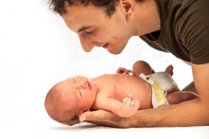 Young Caucasian father leaning over newborn son