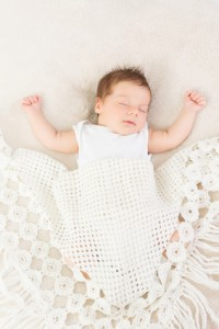 Adorable baby sleeping with hands up