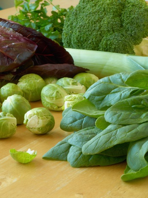 Leafy vegetables - spinach, Brussels sprouts, leeks, parsley, broccoli, lettuce - lying on a wooden table